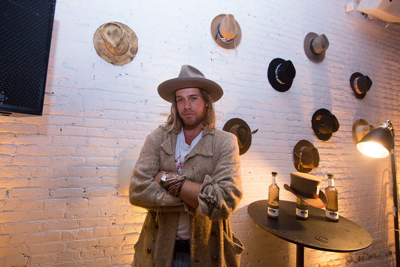 Fashion Hat Designer Nick Fouquet with a collection of hats on display, featured brands