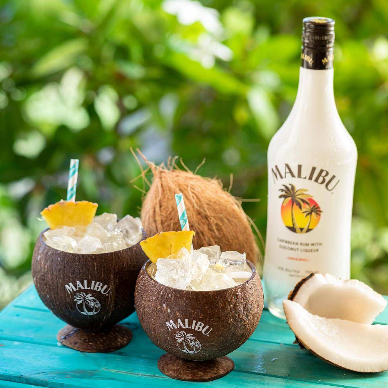 bubbly Piña Colada cocktails in coconuts with bottle