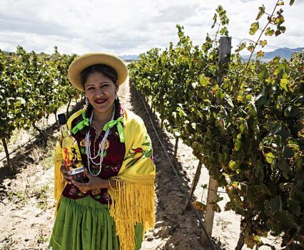 bolivian-woman-with-singani-63-bottle-in-field