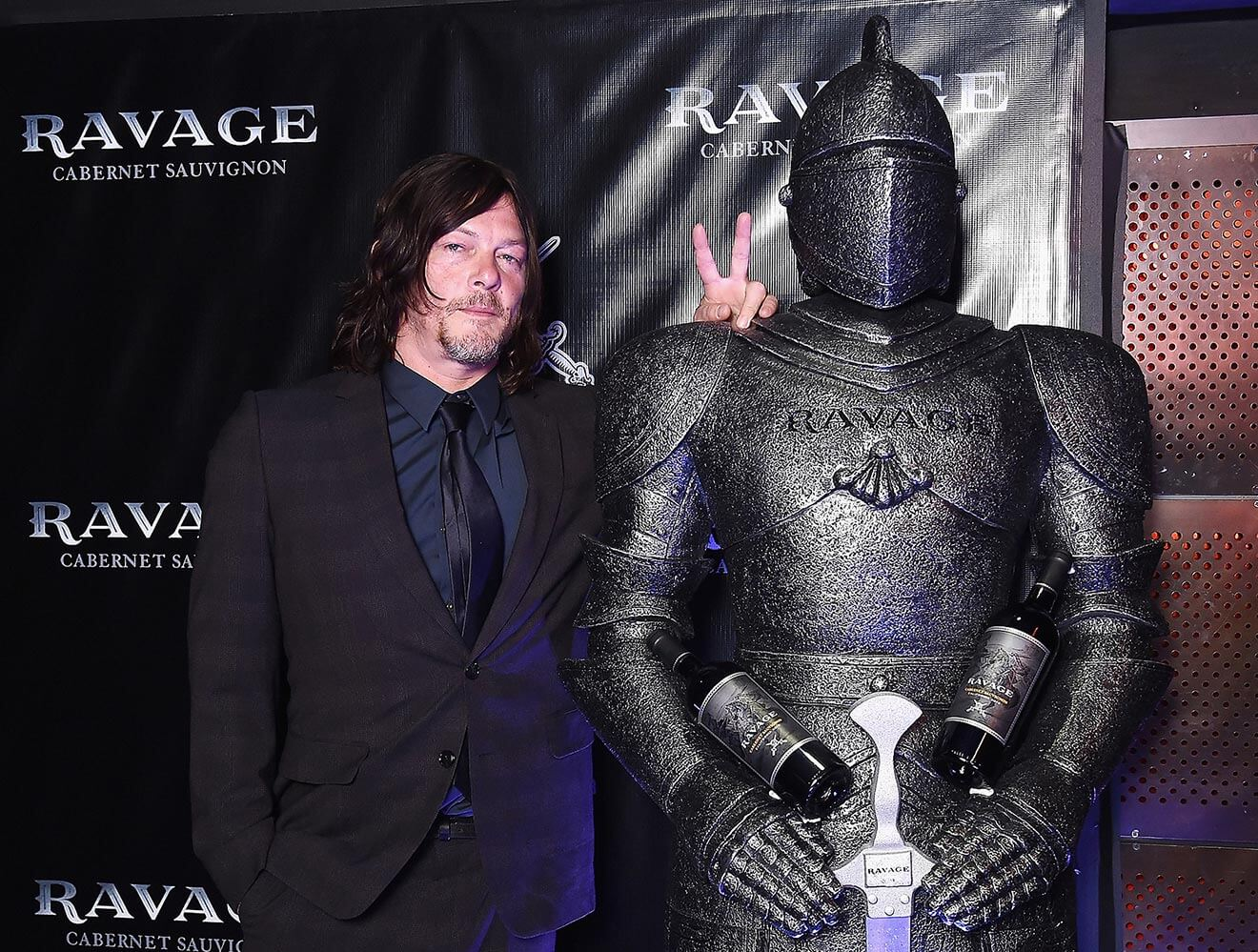 Norman Reedus gets friendly with a Ravage-Wines knight on the black carpet at Comic-Con's Heroes After Dark party