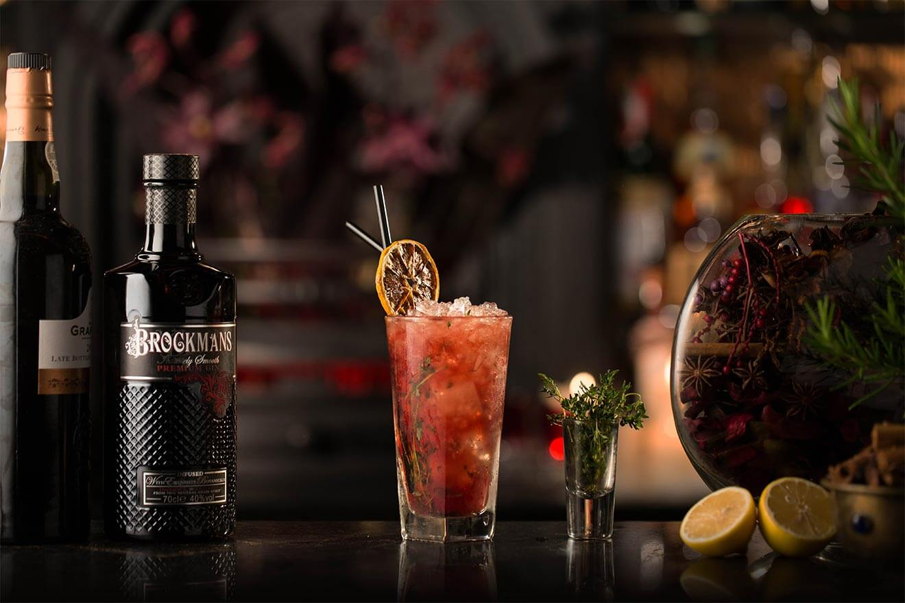 Brockmans Winter Bramble, cocktail with bottle, garnish background