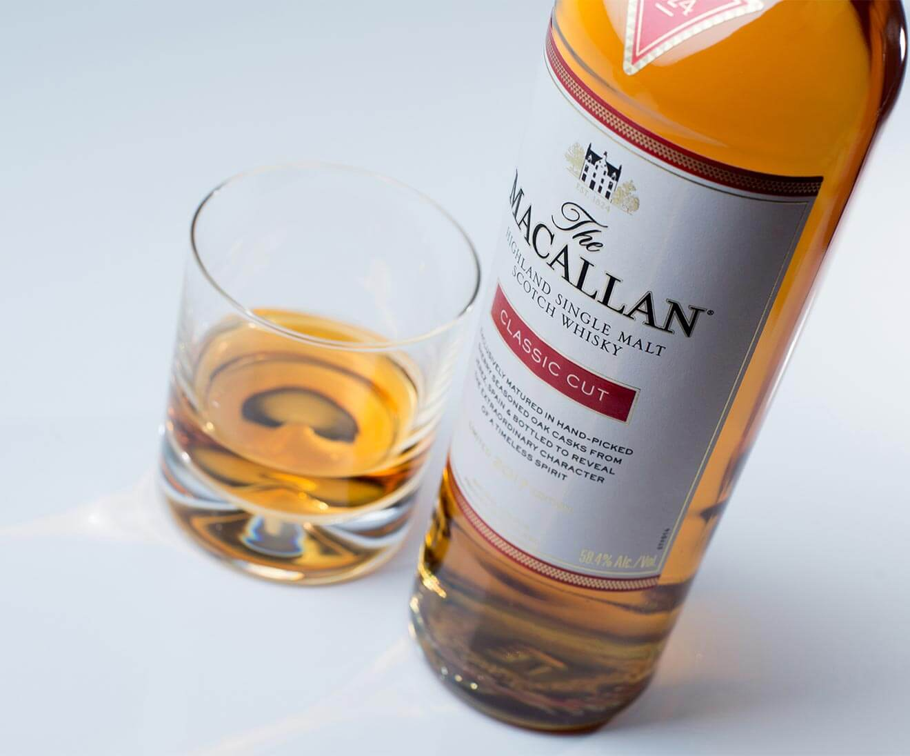The Macallan Classic, with rocks glass, neat pour, on white
