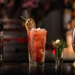 Brockmans Winter Bramble,cocktail with bottle, garnish background, featured image