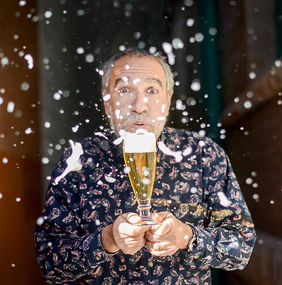 Charlie Papazian, blowing foam off the top of a beer