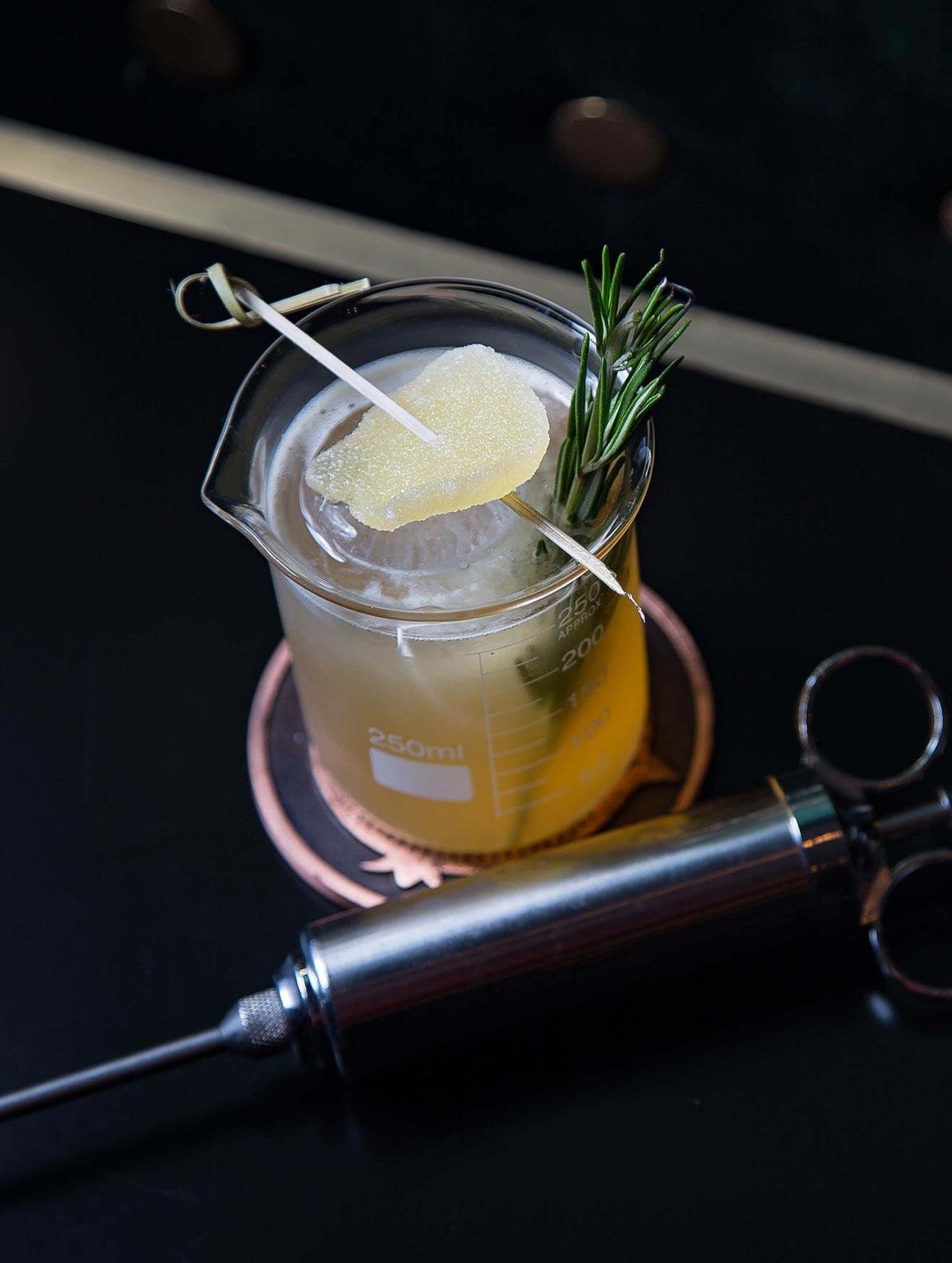 The Peaty Penicillin Cocktail, dark back with syringe and garnish