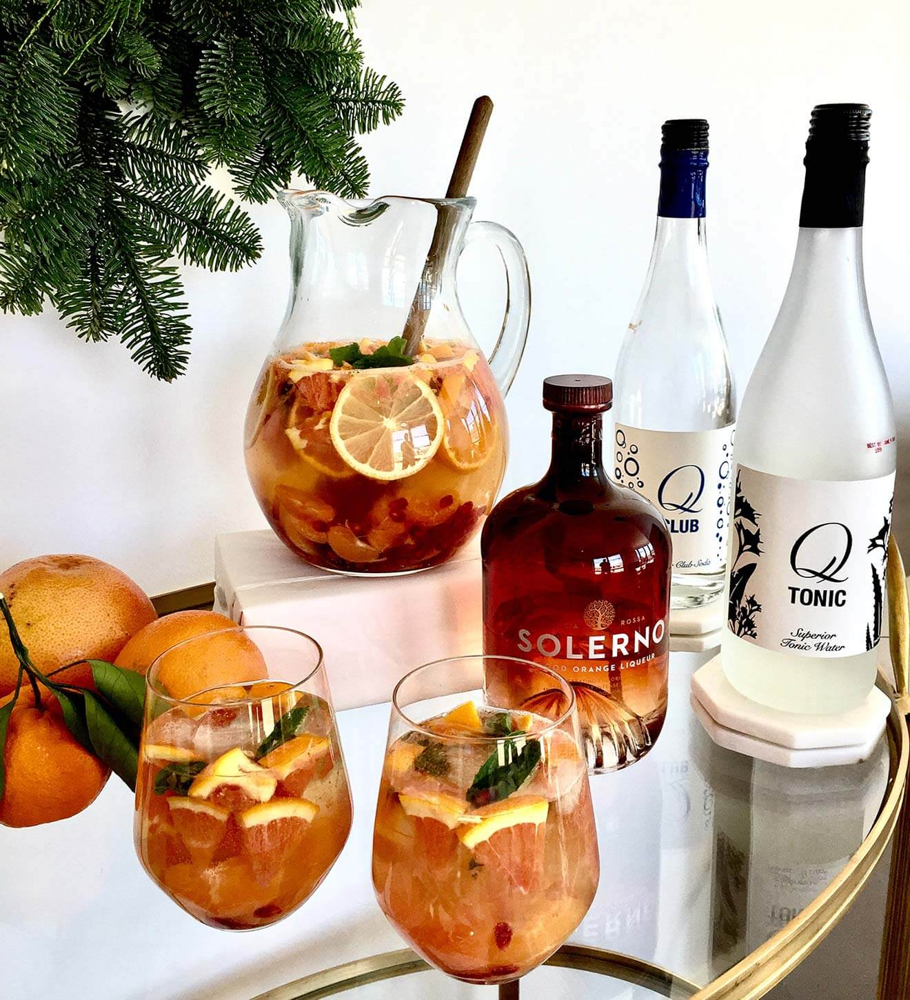 Winter Citrus Sangria cocktails with bottles and garnish