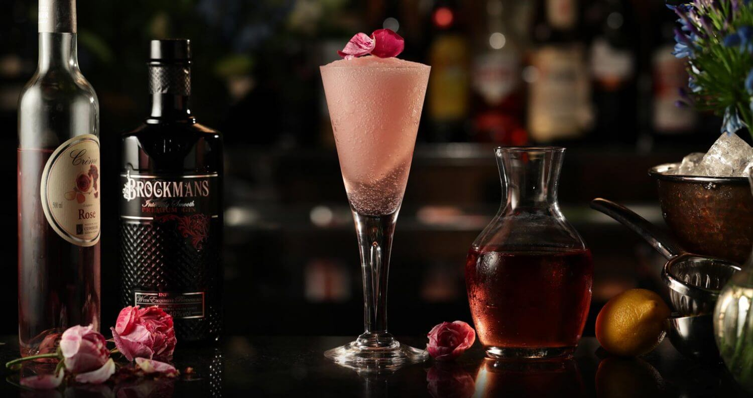Brockmans Frosé, with bottles, cocktail, garnishes on dark, featured image
