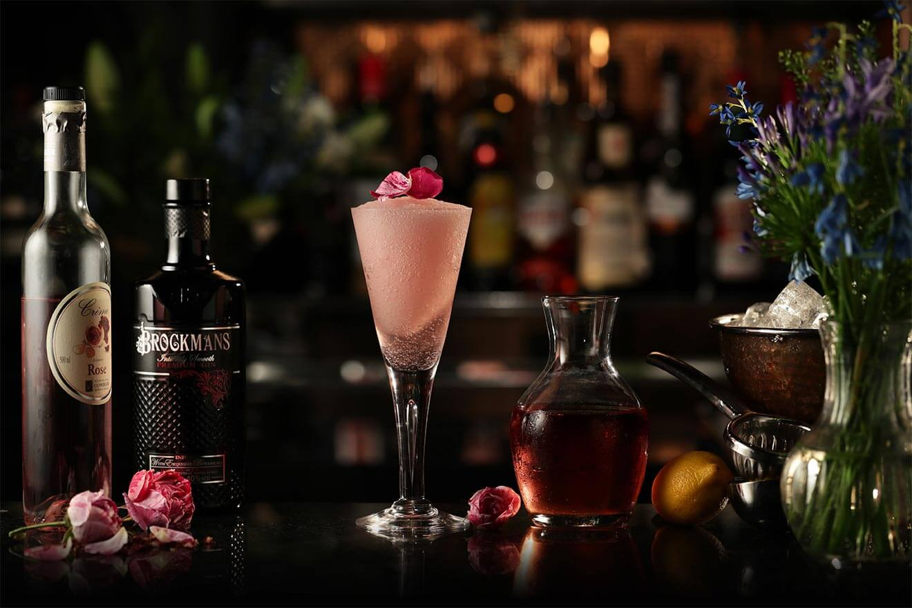 Brockmans Frosé, with bottles, cocktail, garnishes on dark