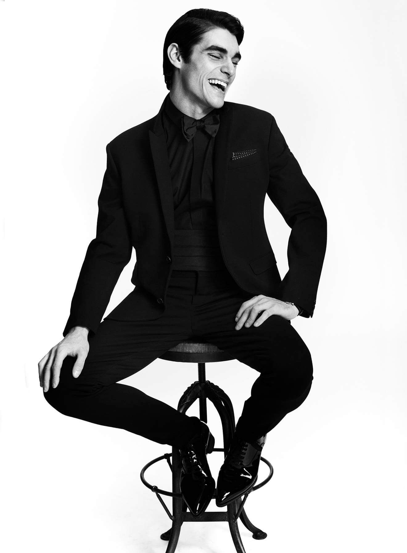 Chillin' with RJ Mitte, black and white, smiling on stool, tux