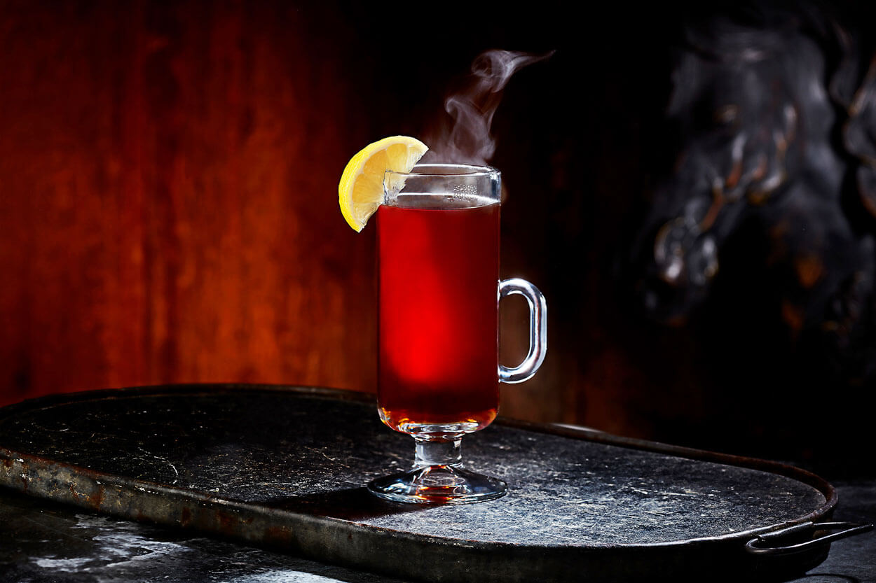 Rooibos Toddy, on dark background, cocktail with lemon garnish