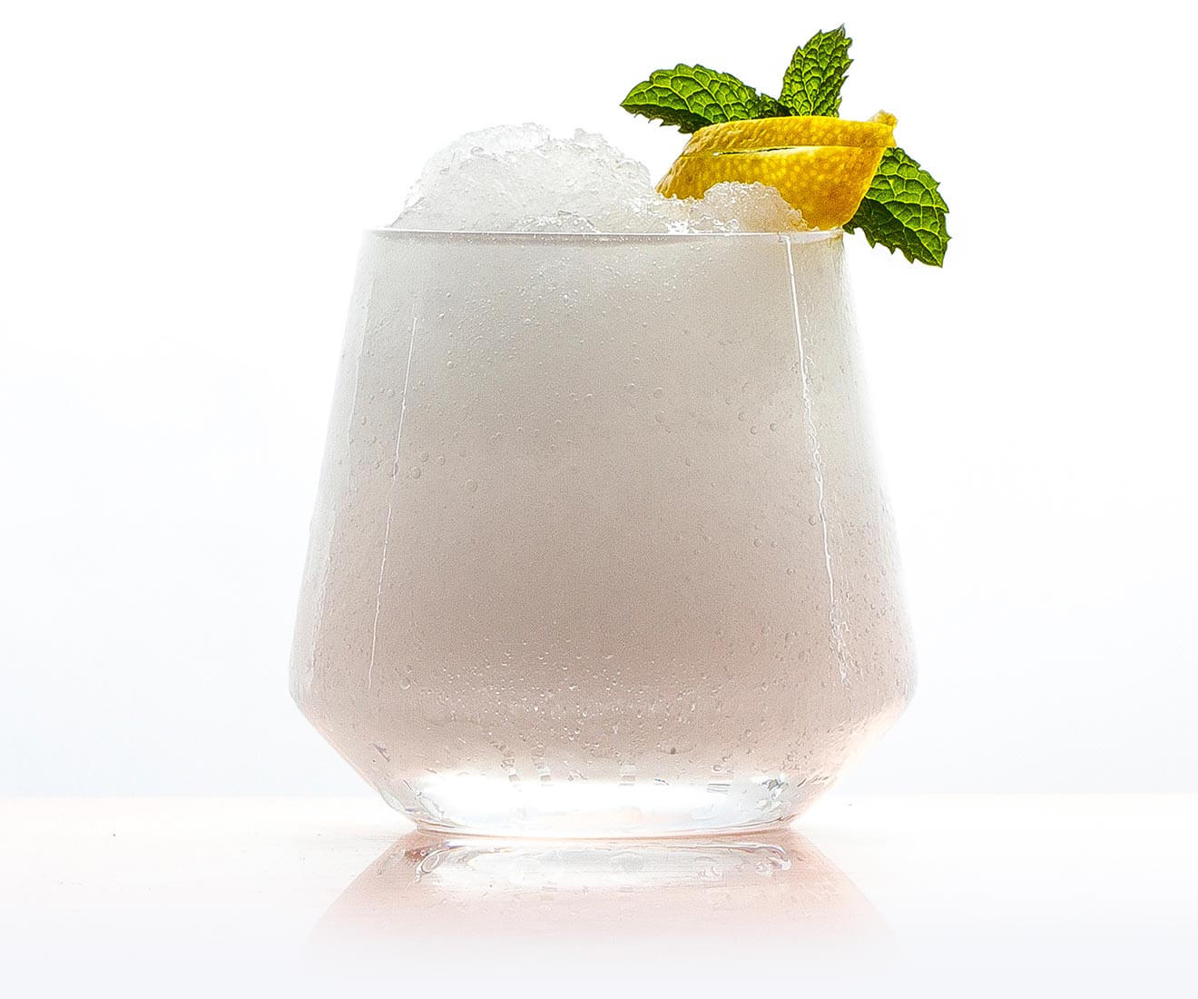 Absinthe Frappe, cocktail with garnish on white