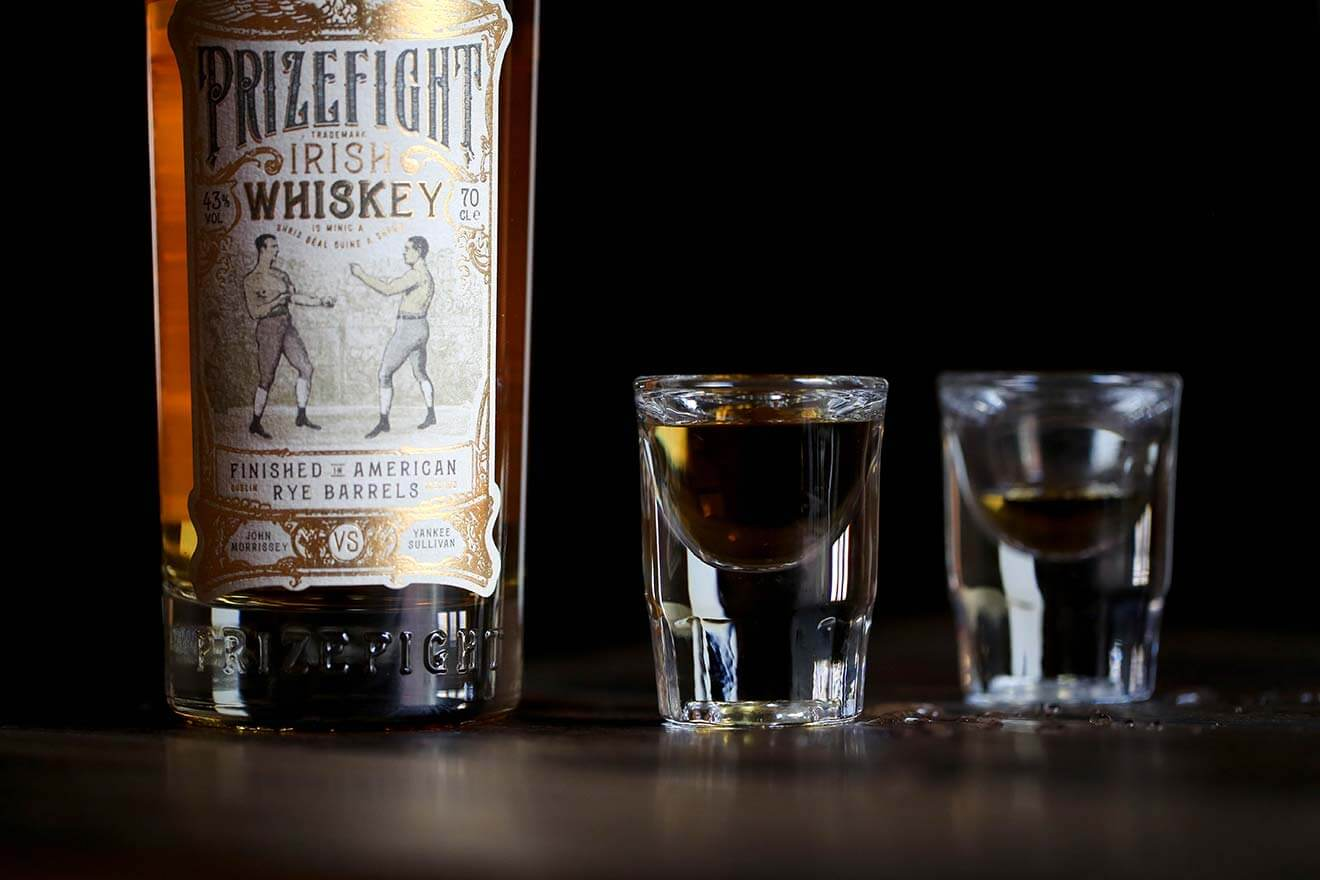 Prizefight Irish Whiskey, bottle and shots on dark back