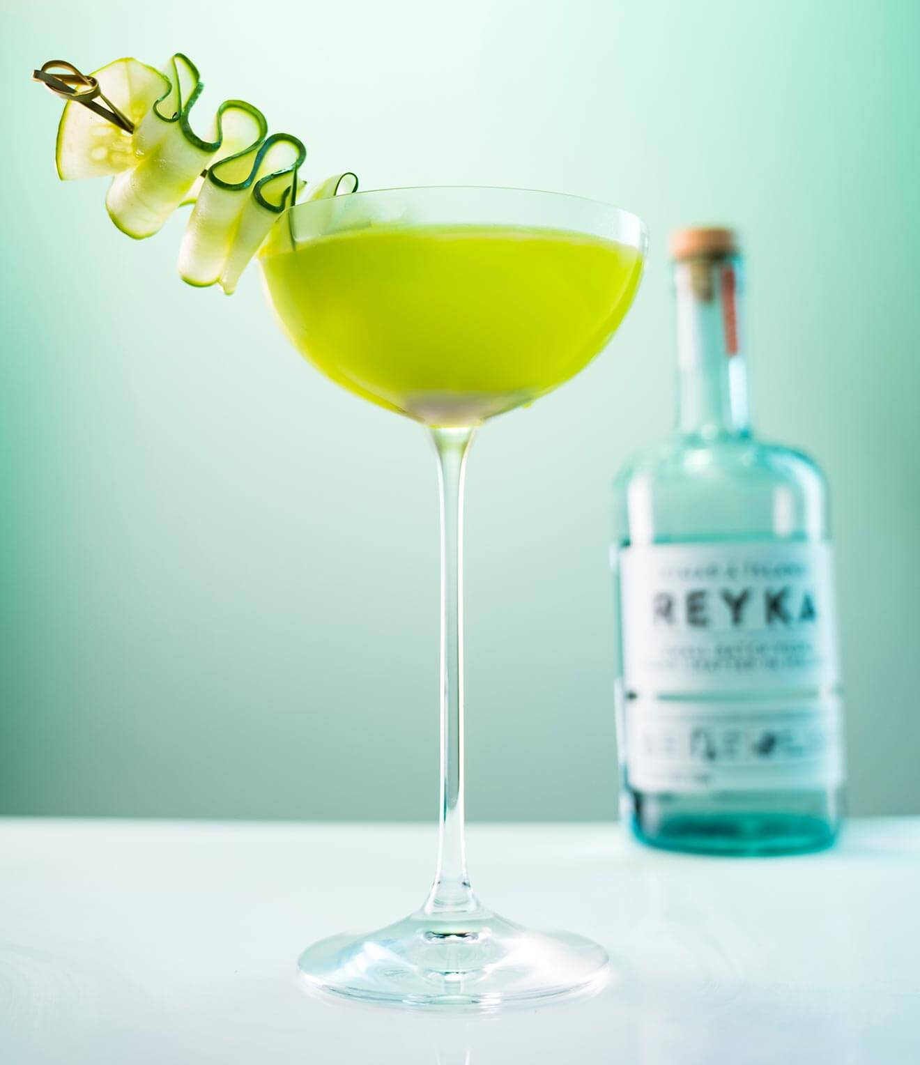 The Sophisticated Shamrock, cocktail with cucumber garnish and bottle