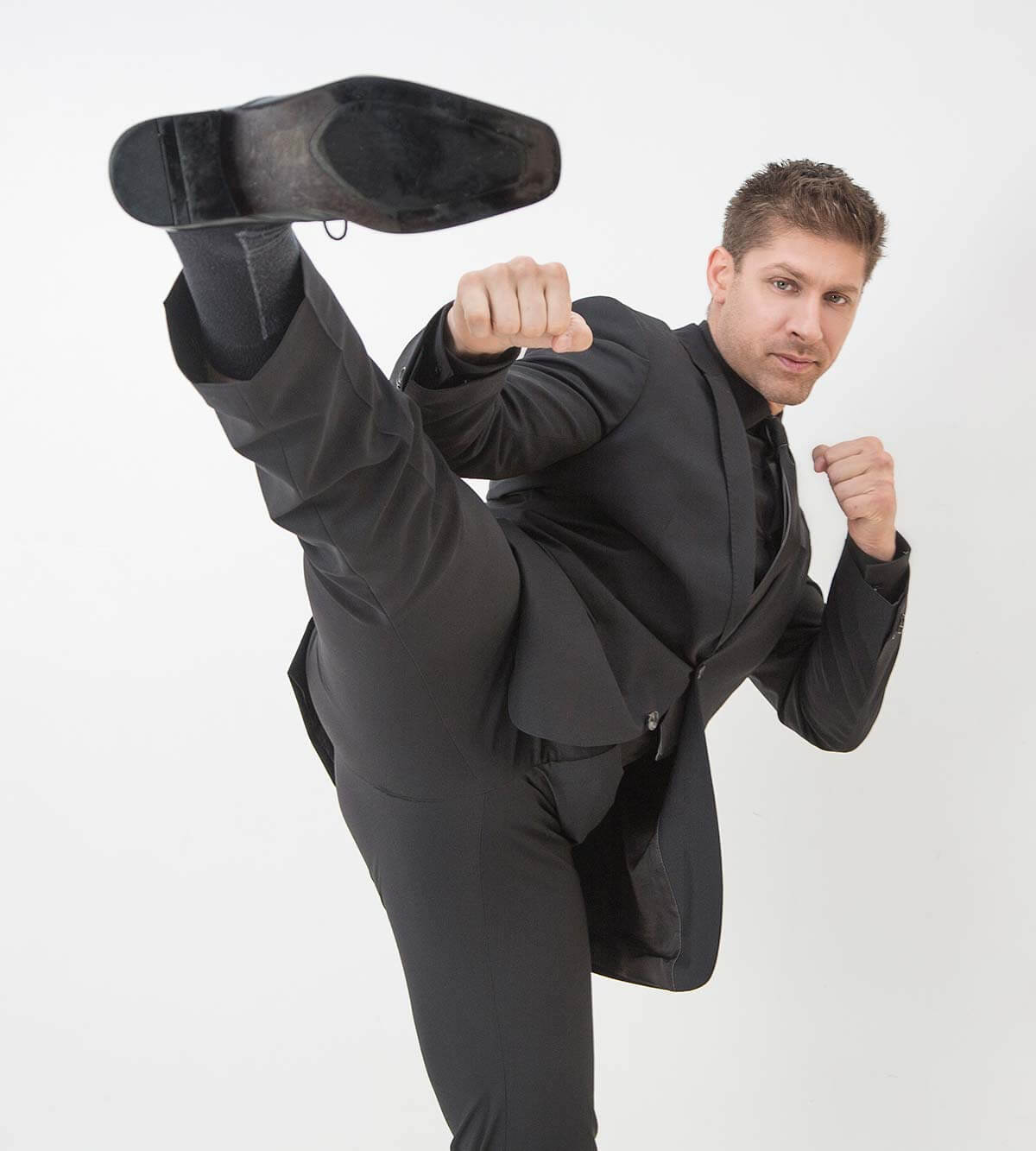 Chillin' with Alain Moussi, high kick in black suit, on white