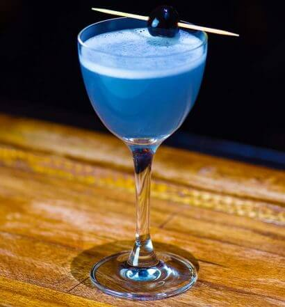 aviation cocktail with garnish, wood table, featured image
