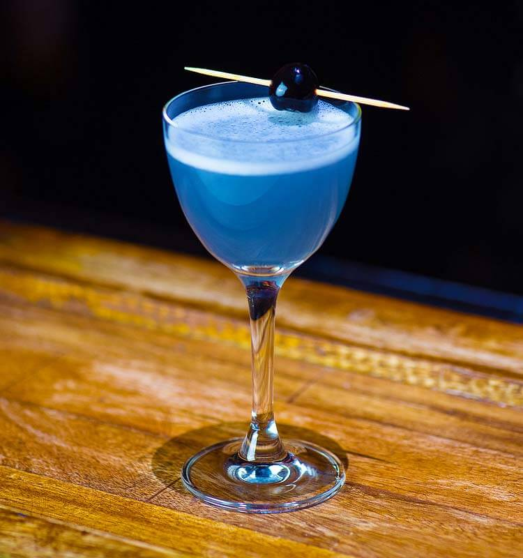 aviation cocktail with garnish, wood table