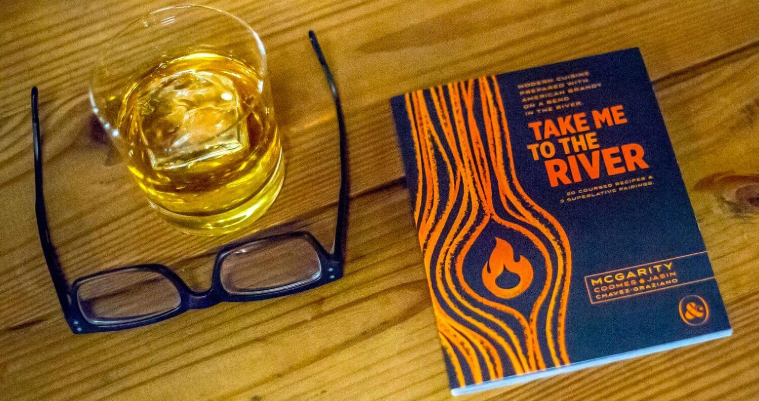 Take Me to the River, book, glass of neat brandy on table, featured image