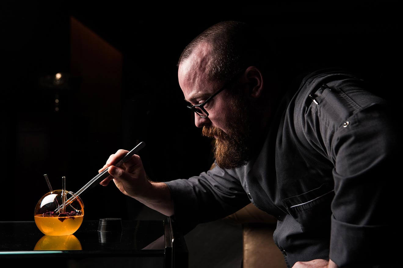 bob peters of charlotte nc, mixing a gourmet cocktail, dark background