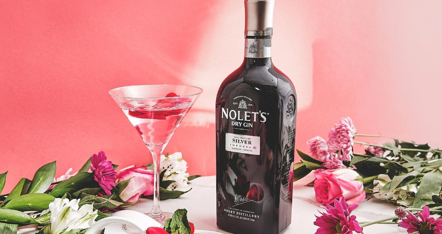 Rose Gimlet Raindrop Cake, martini and bottle with garnishes on table, pink lighting, featured image
