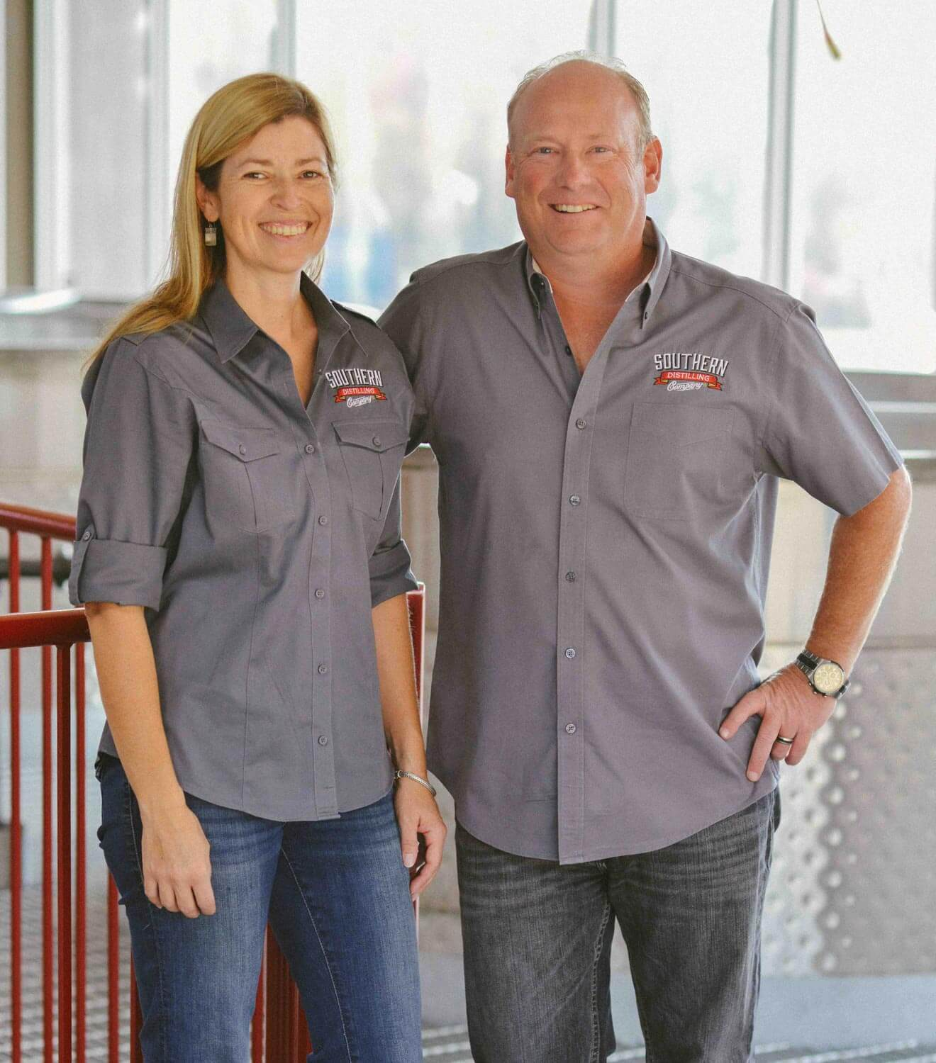 Vienna and Pete Barger of Southern Distilling Co., couple in distillery in uniform