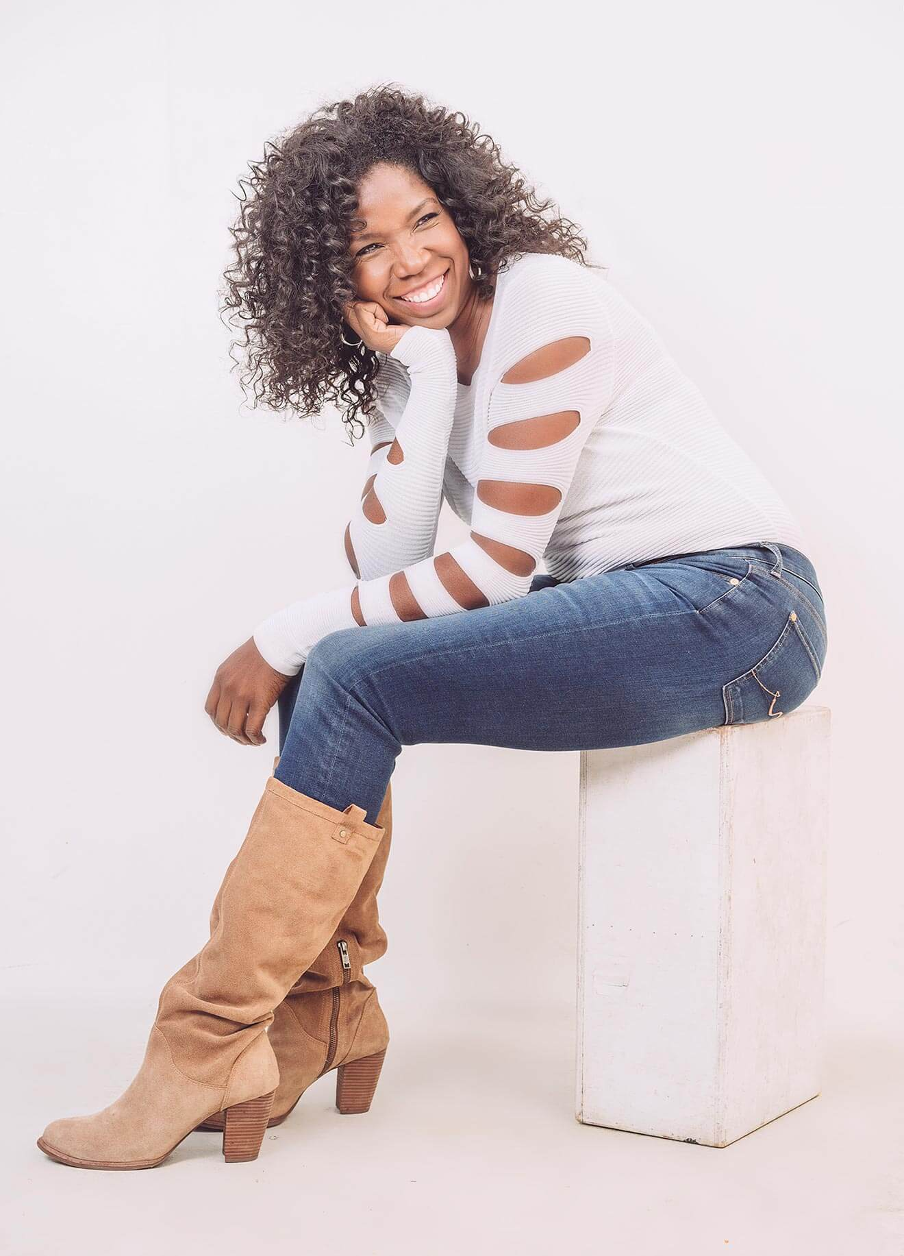 Chillin' With Nicki Micheaux, jeans and tall boots on stool