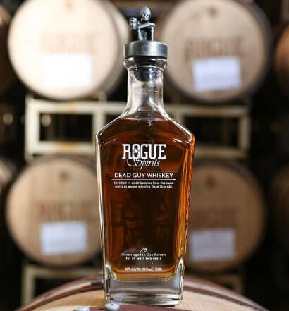 Rogue Ales distiller, whiskey bottle on barrel, barrel room background, featured image