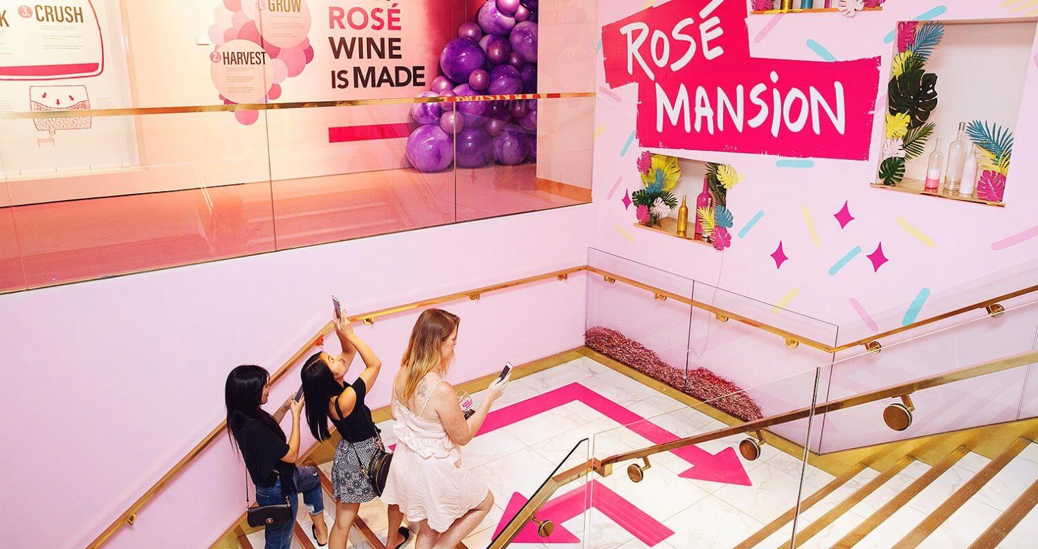 Rosé All Day at Rosé Mansion, girls ascending staircase, snapping photos, featured image