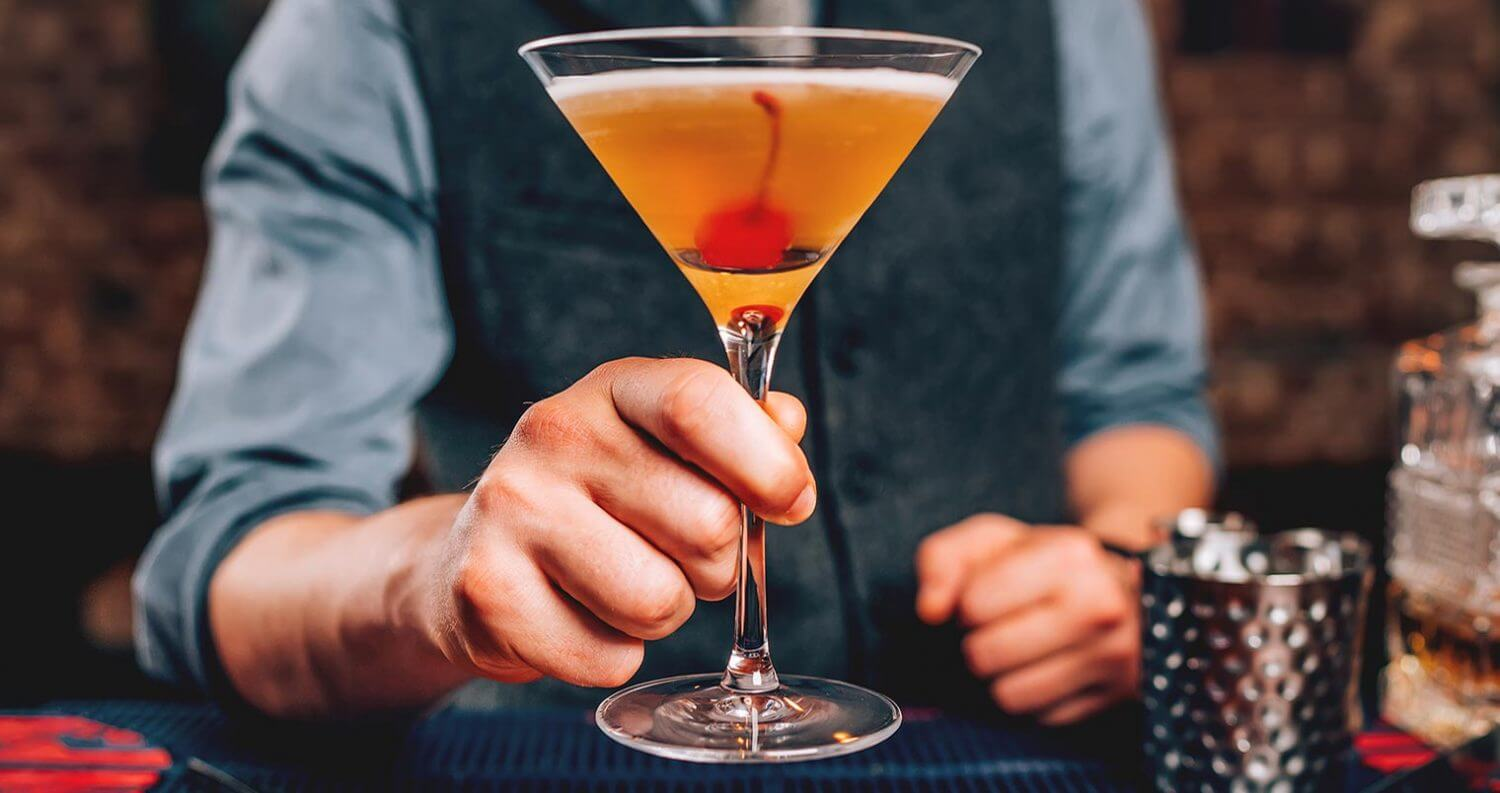 Manhattan Month 2018, bartender holding manhattan cocktail, featured image