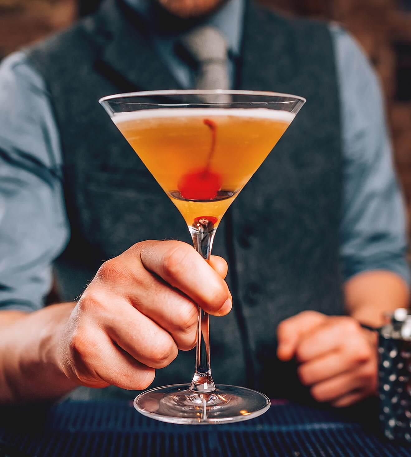 Manhattan Month 2018, bartender holding manhattan cocktail