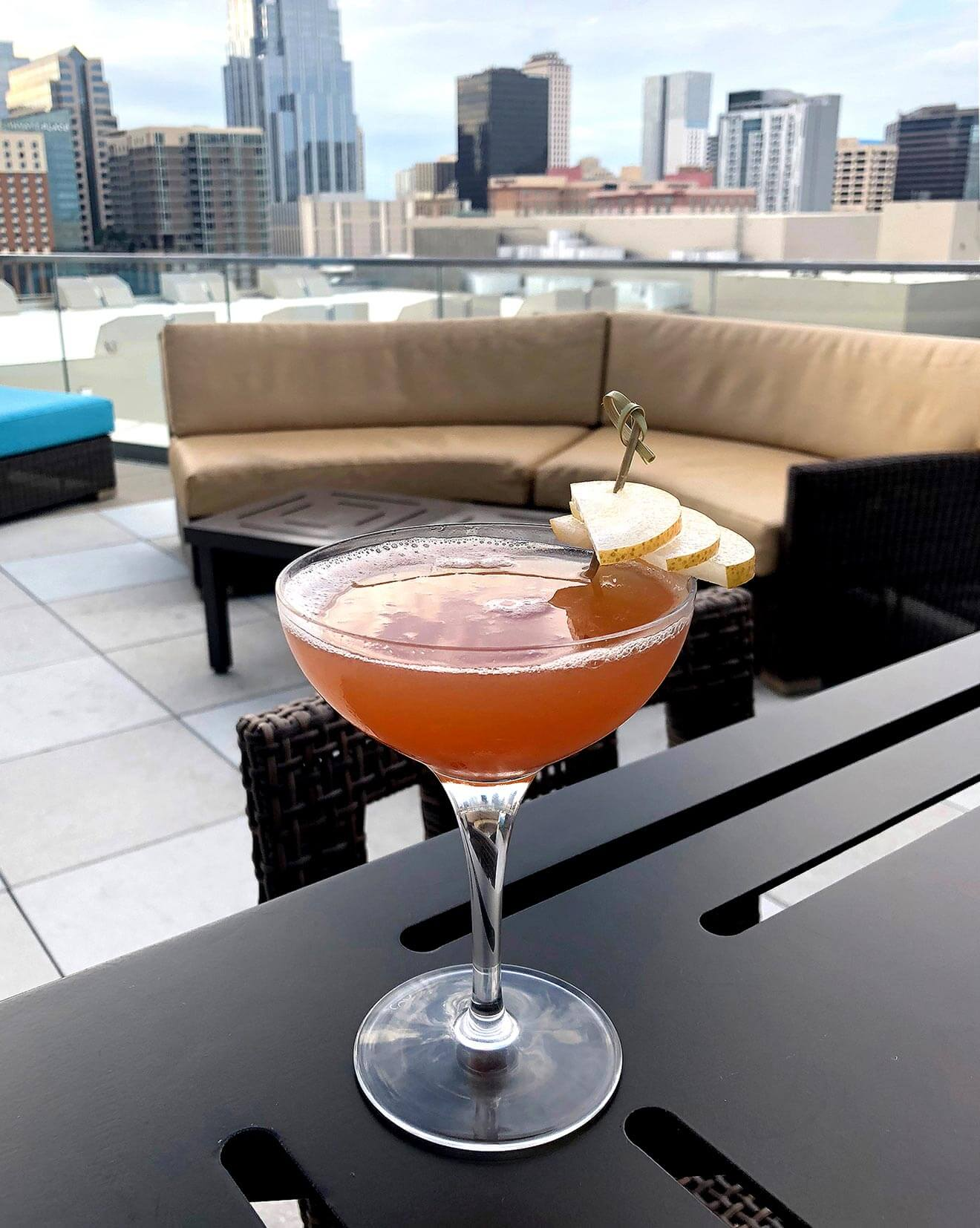 The Golden Hour cocktail on rooftop lounge, city background