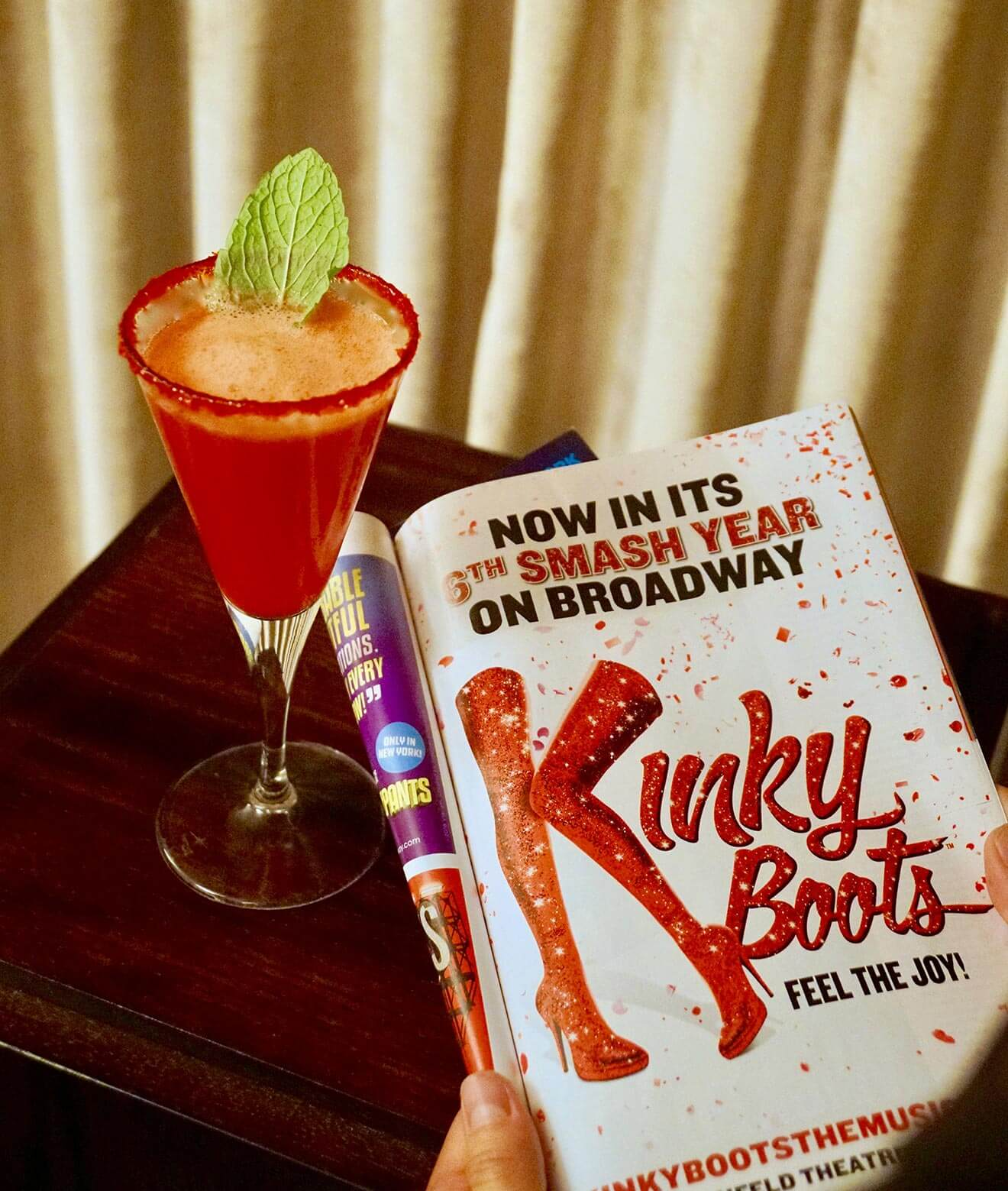 The Shaken Stiletto, Kinky Boots, cocktail and book on table with curtain in back