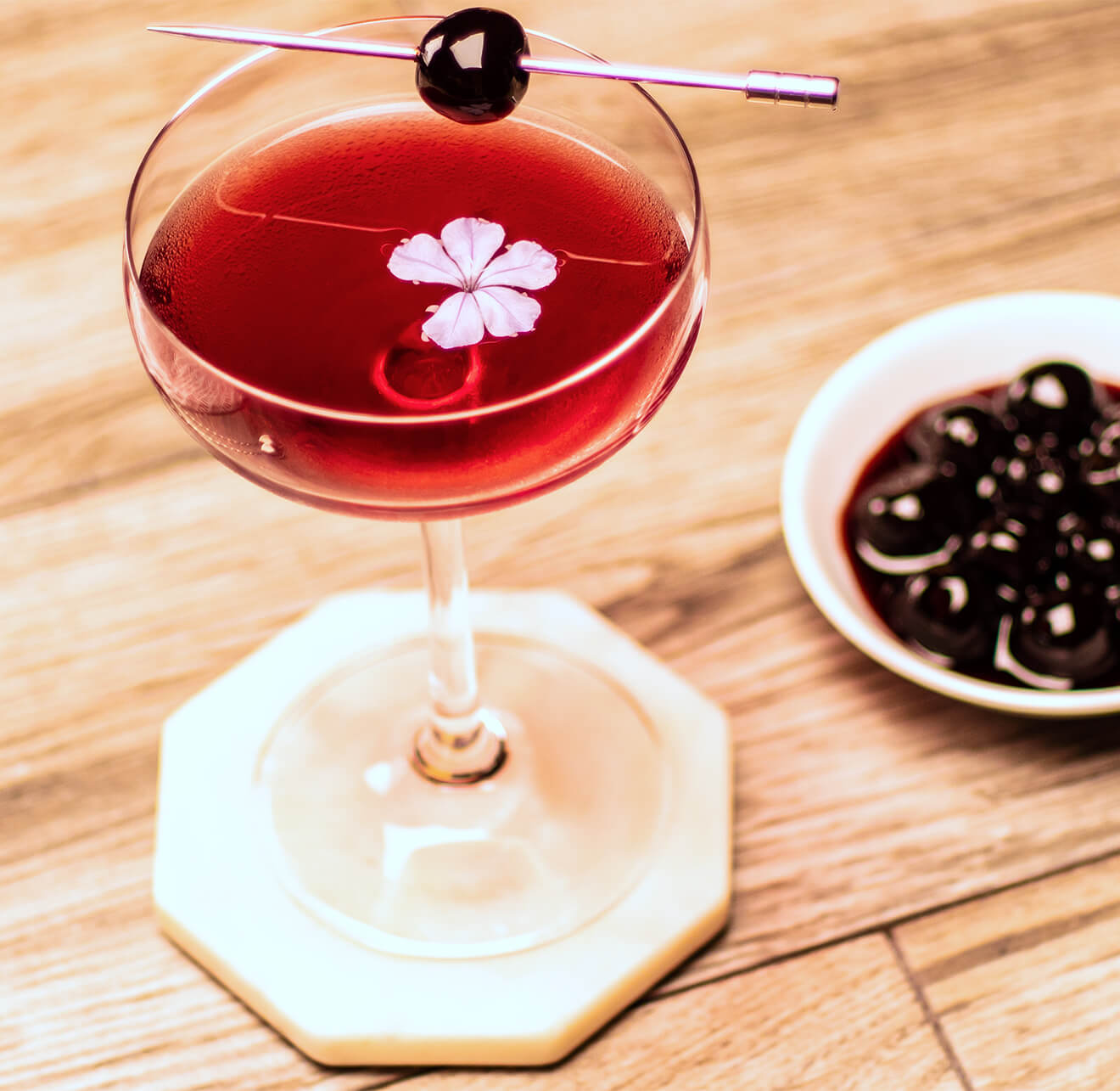 american pie manhattan cocktail with flower garnish