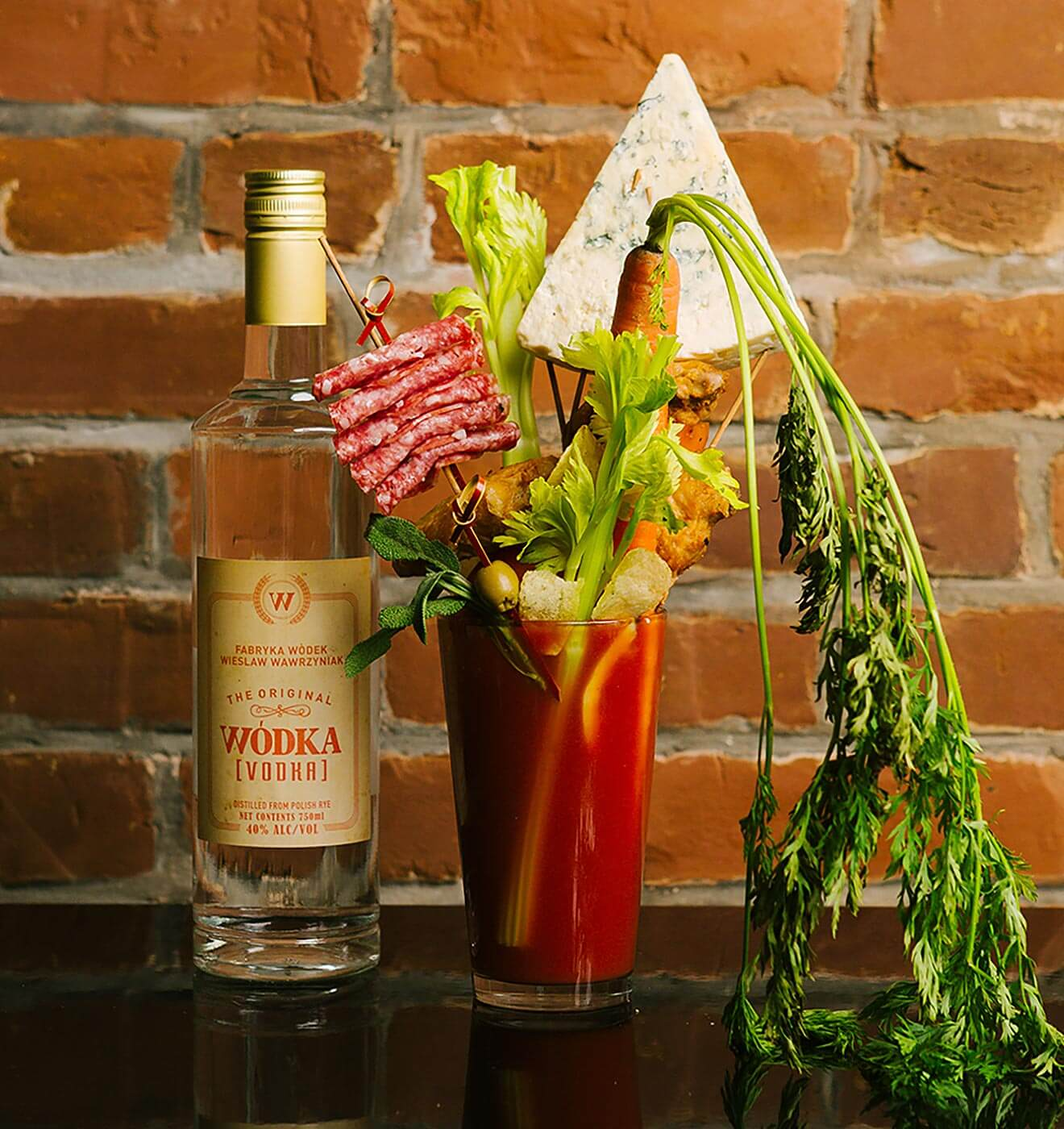 Wódka Bloody Mary, bottle and lots of garnish, brick wall background