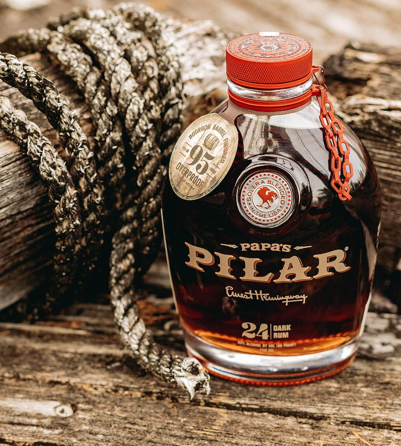 Papa's Pilar Limited Edition Bourbon Barrel Finished Dark Rum, bottle and rope decoration, wood table