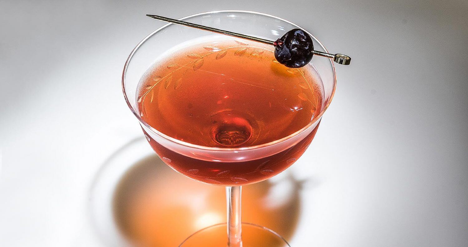 Surfer Rob Roy cocktail with toothipick garnish, featured image