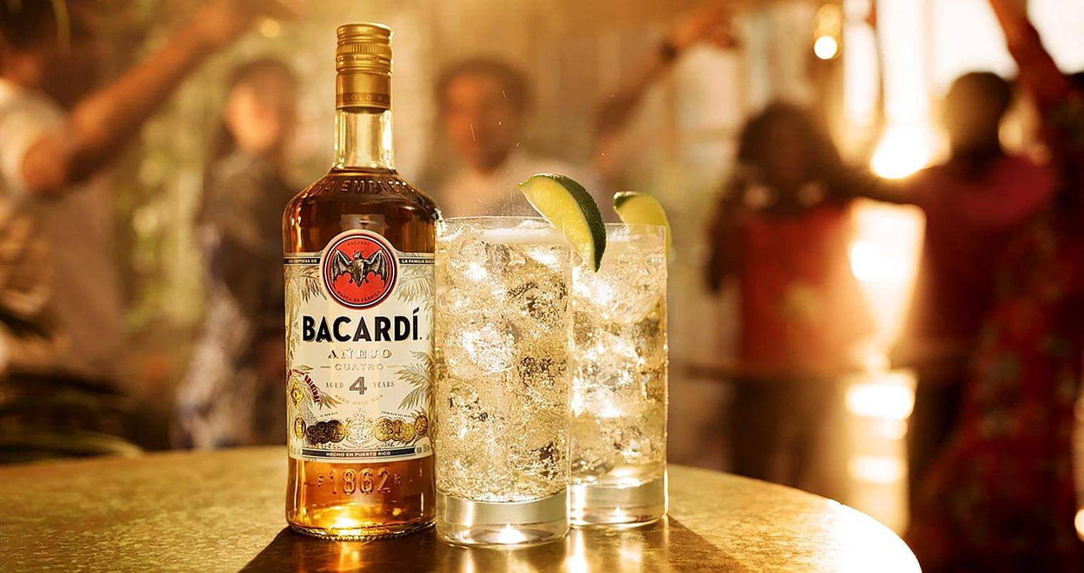 BACARDÍ Cuatro mismo, bottle and cocktails, people dancing in back, featured image