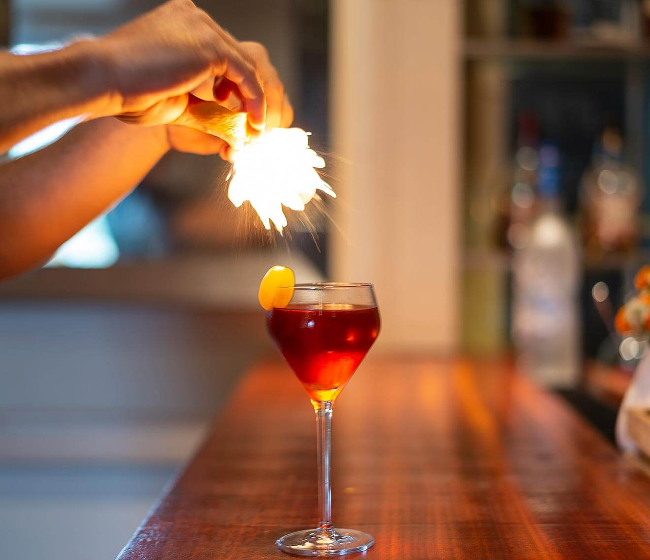 Eau de Vie cocktail with bartender adding garnish with flare