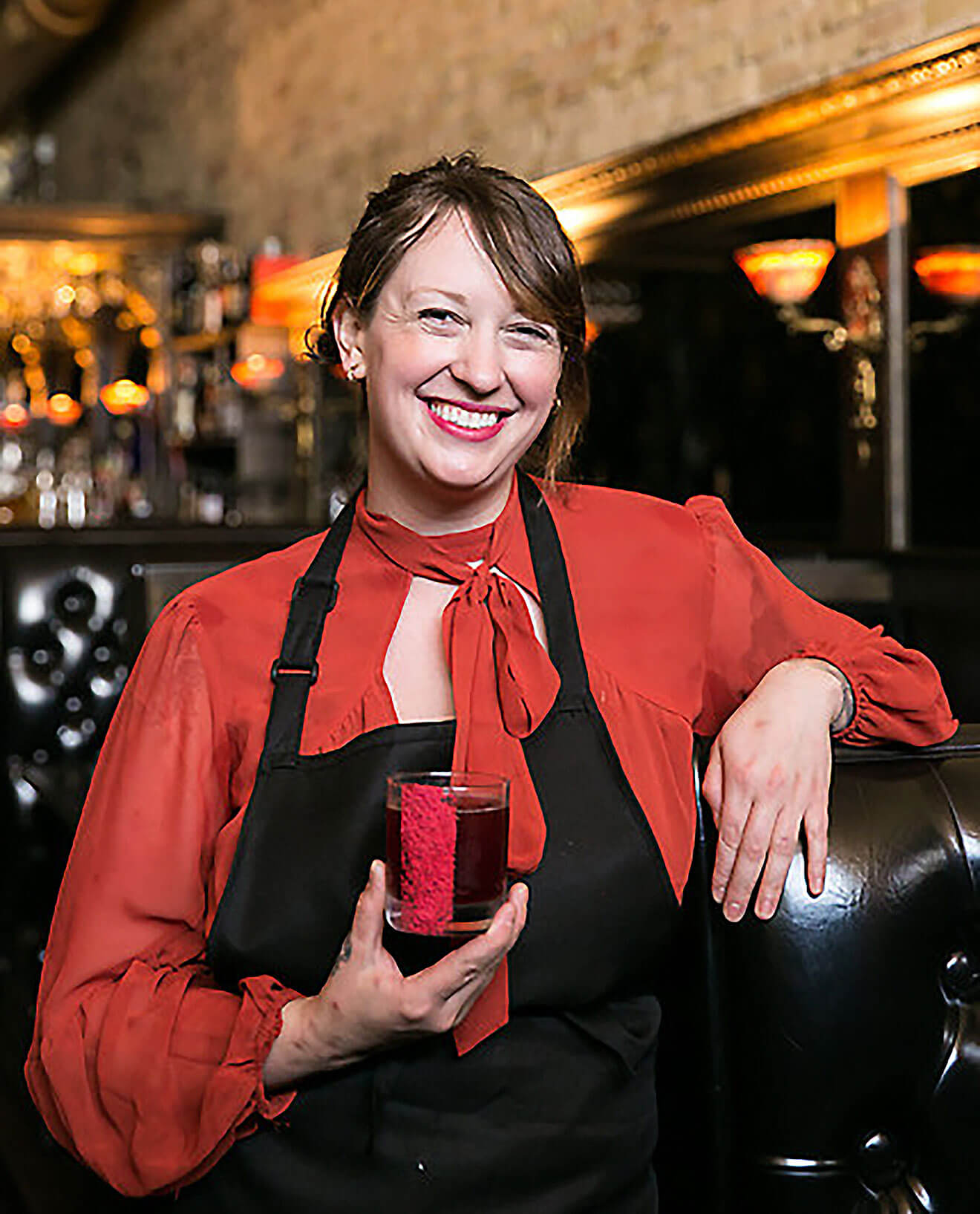 Tacy Rowland, side of the bar, presenting cocktail