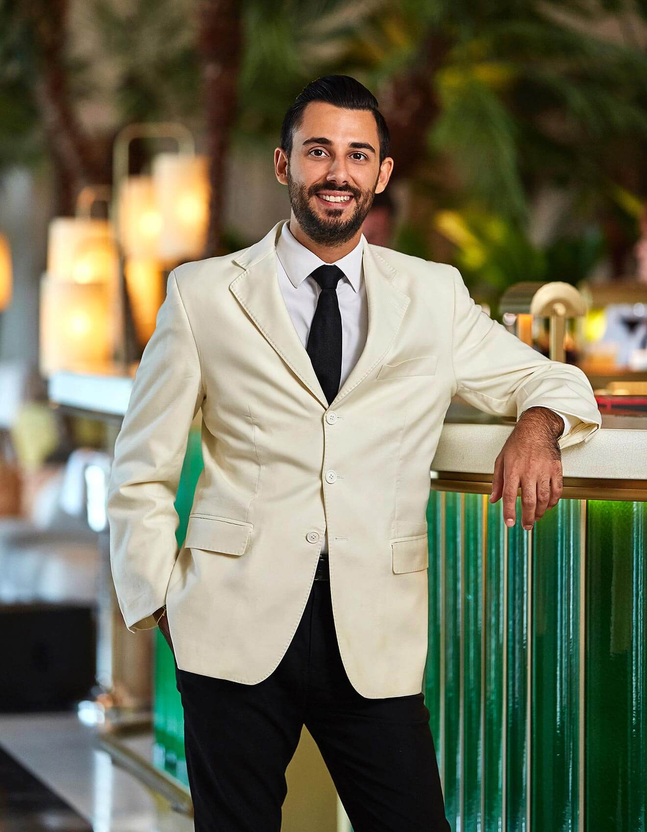 Valentino Longo - Chilled 100 Member, Miami, portrait, cream colored suit, green fence