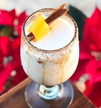 White Christmas, cocktail with garnish, red poinsetta display
