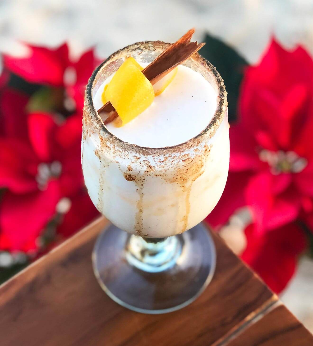 White Christmas, cocktail with garnish, red poinsetta display, featured image