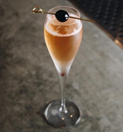 Don't Dream It, Be It, cocktail with garnish on granite table, featured image