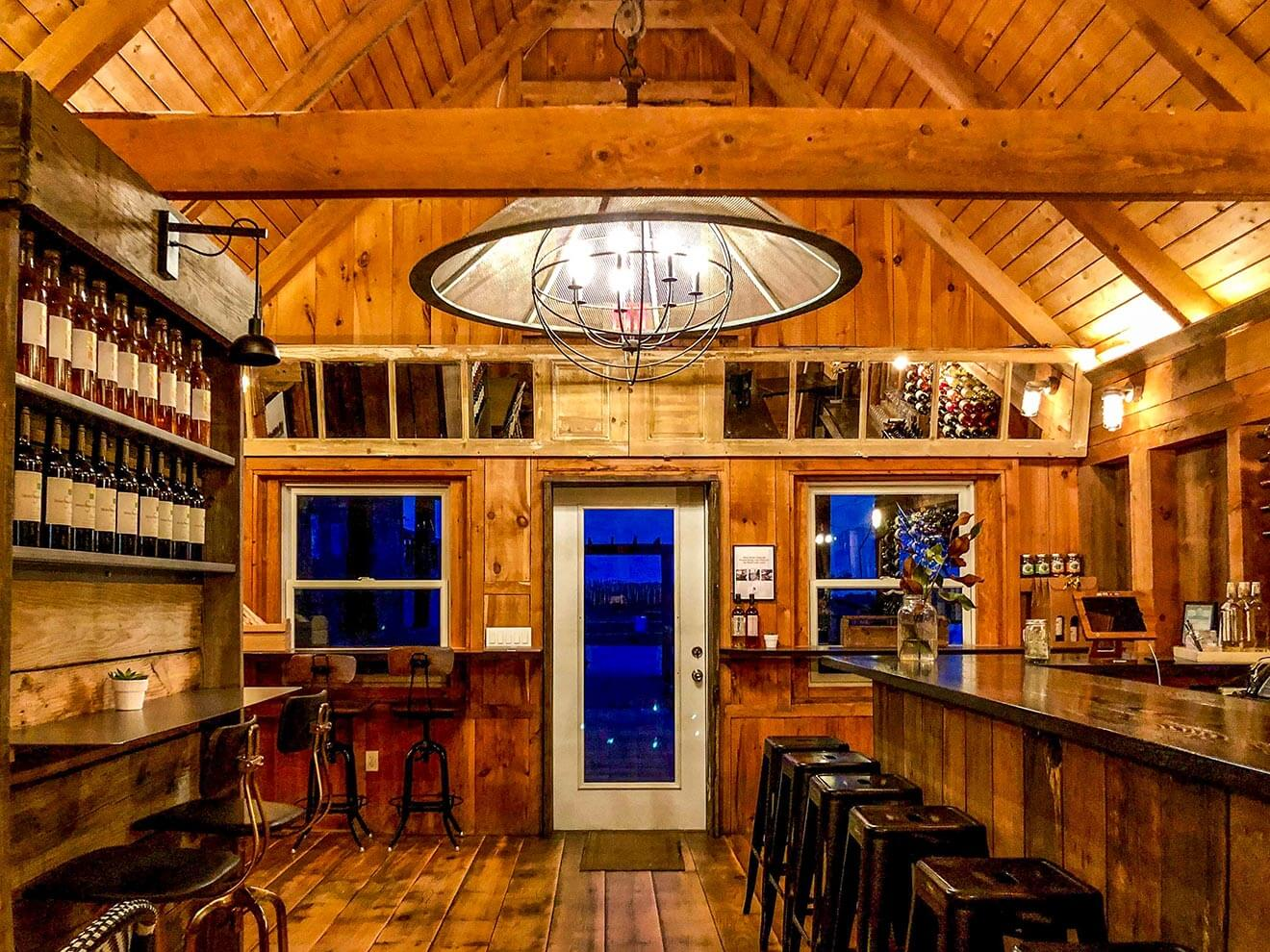 Shinn Estate Tasting Patio, room with wood paneling, bottles on shelves
