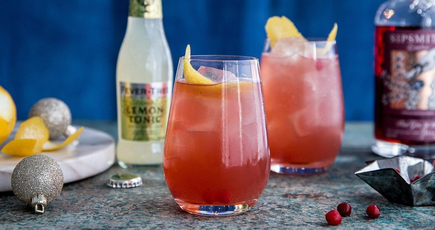 Sloe Gin & Fever-Tree Lemon Tonic, cocktails and bottle, blue starry backdrop, featured image