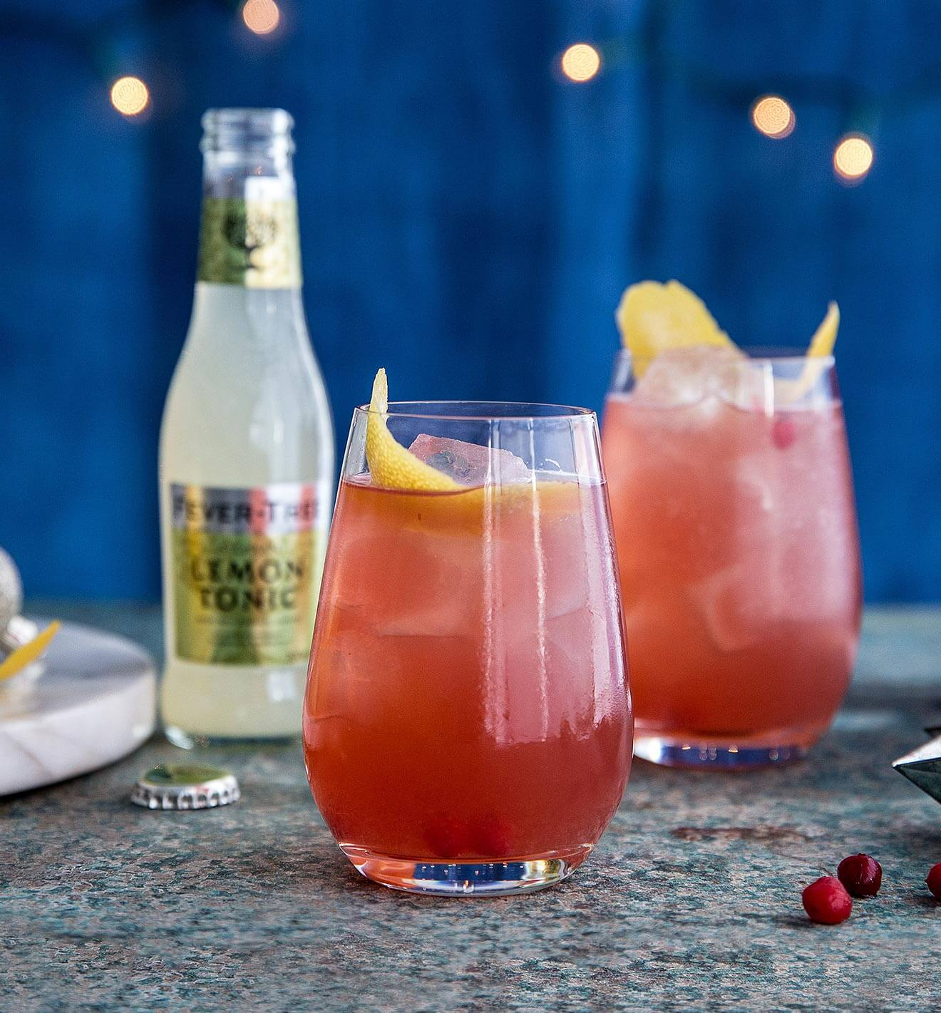 Sloe Gin & Fever-Tree Lemon Tonic, cocktails and bottle, blue starry backdrop