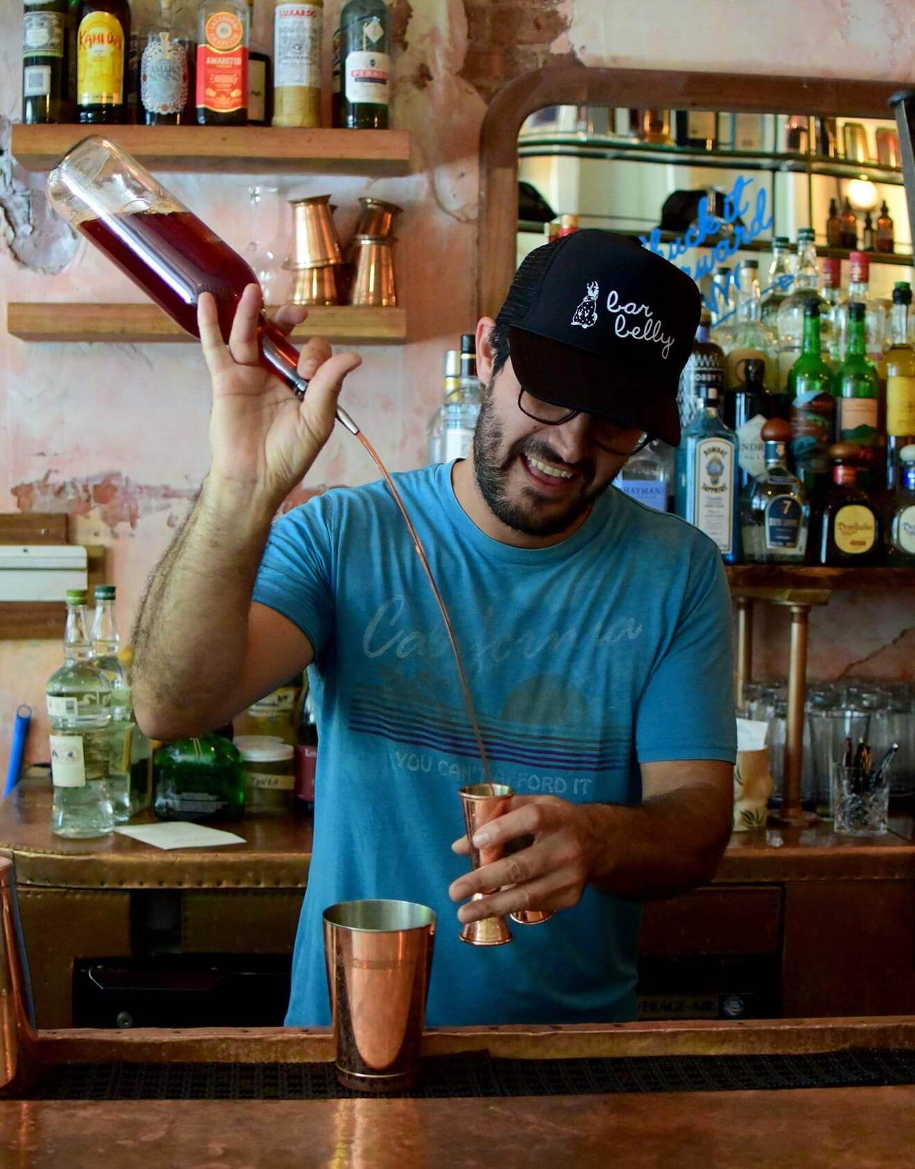 Federico Avila Pouring with a Jigger, behind the bar smiling