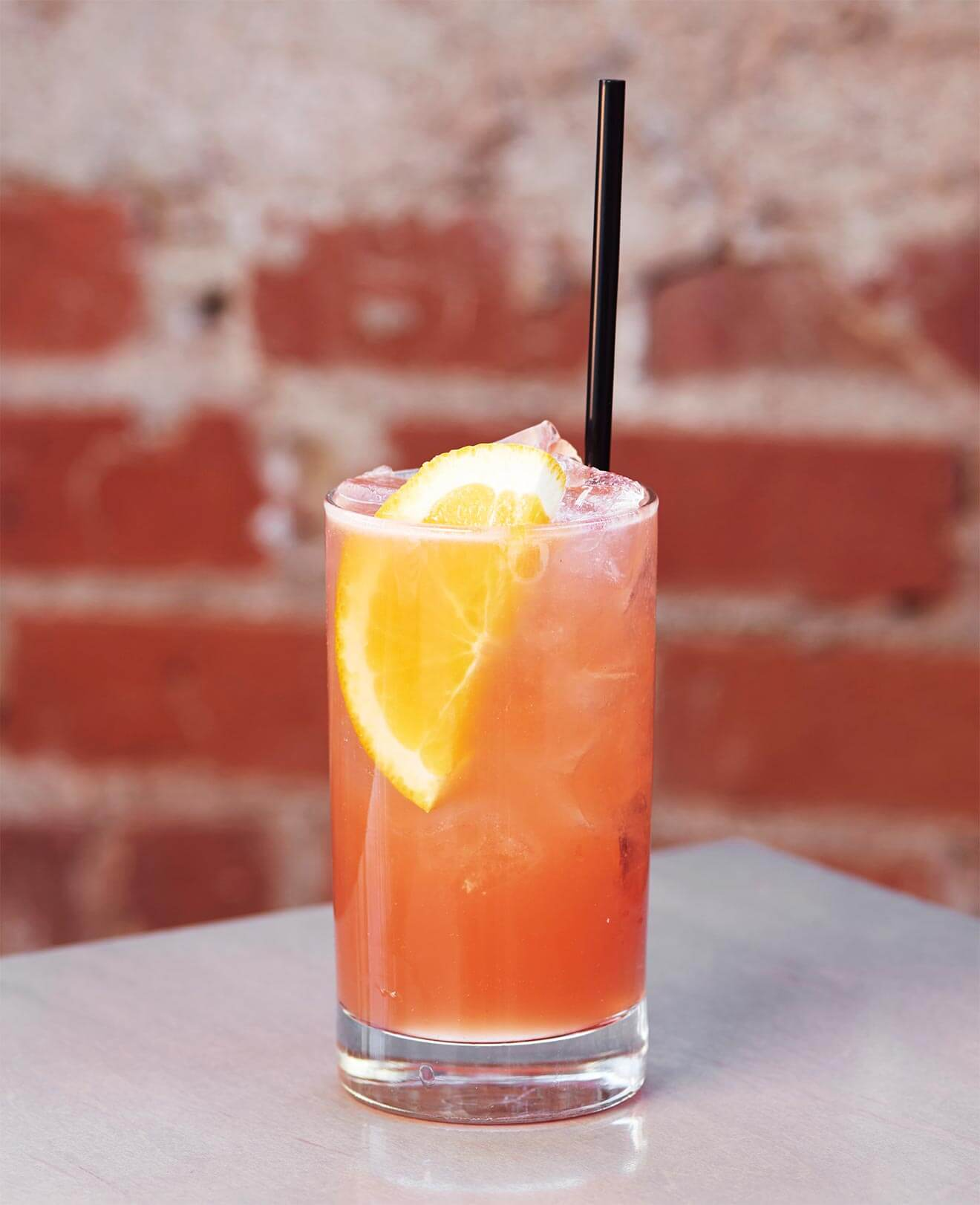 #1 Crush, cocktail with garnish and straw, brick wall background
