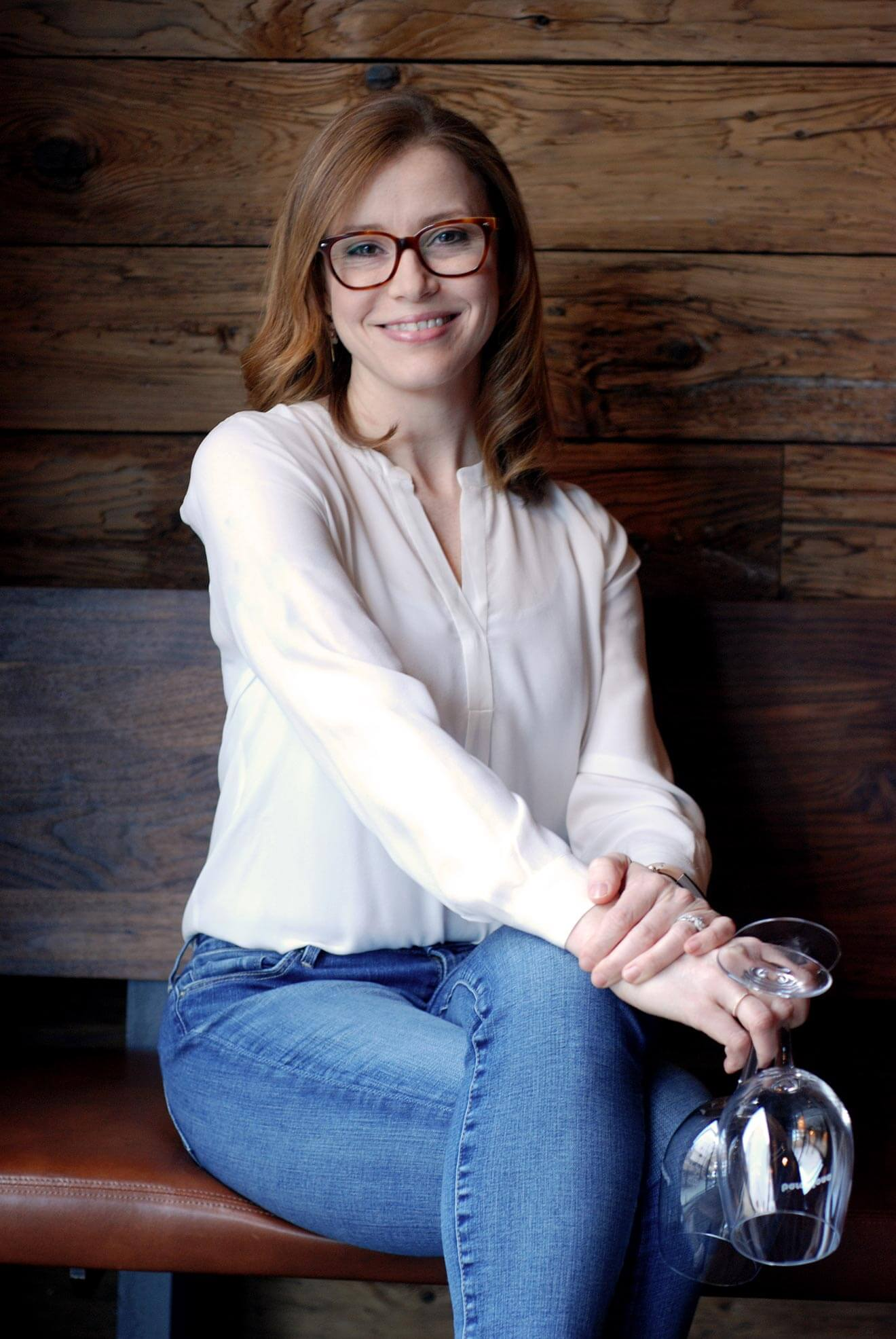 Gretchen Thomas posing with wine glasses on wooden bench