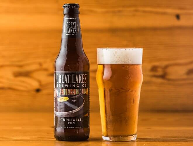 Great Lakes Brewing Co. Turntable Pils, bottle and glass, wood background