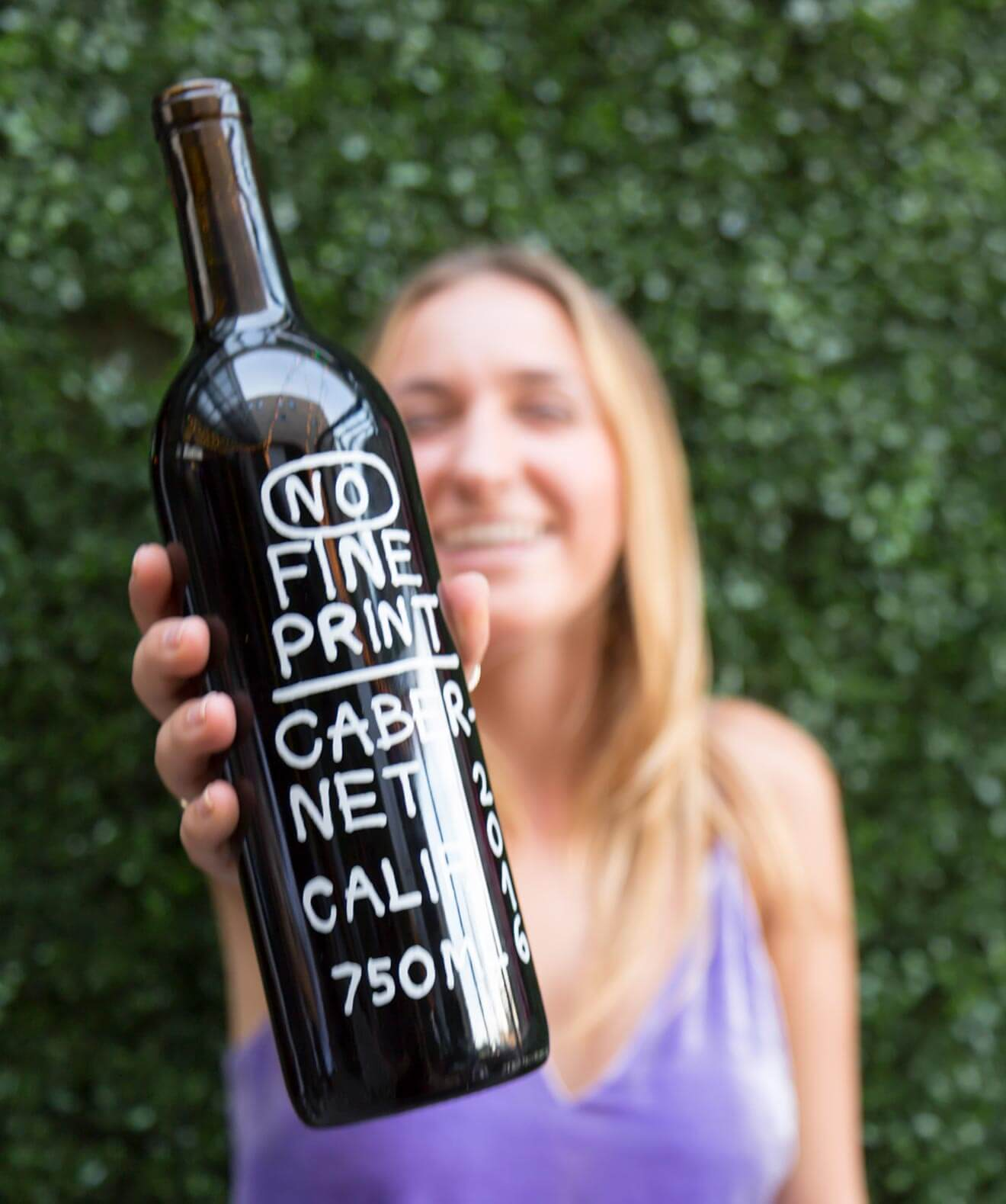 No Fine Print Wine, girl holding up bottle